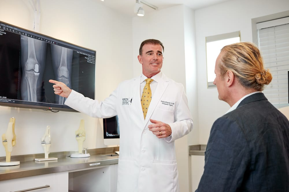 NYC Robotic Knee Surgeon Dr. Buechel reviewing knee imaging and discussing knee replacement procedure with his patient.