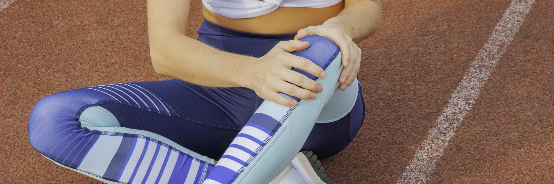 An injured sportswoman sitting on the running track and touching the painful knee area.