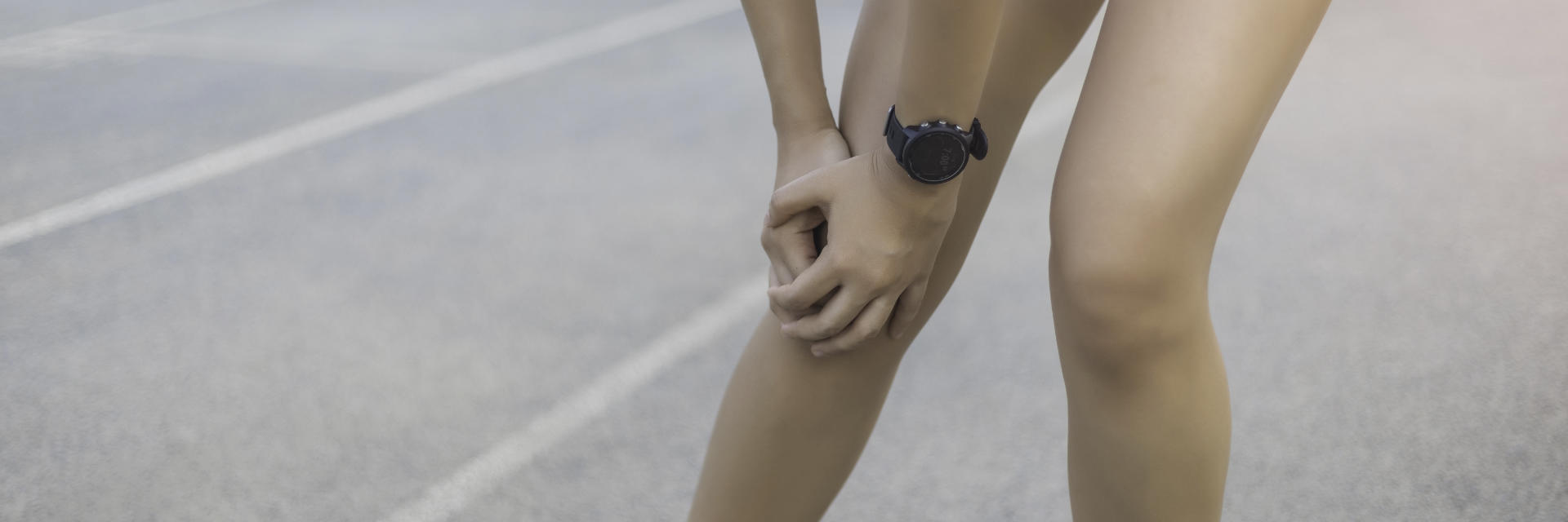 An sportsperson standing on the running track and touching the painful knee area.