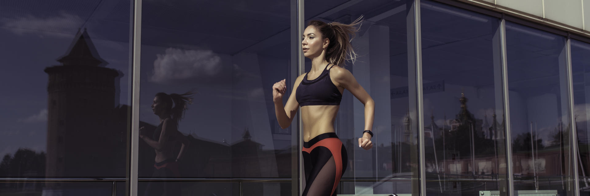A fit young woman running along an office building with glass window wall.