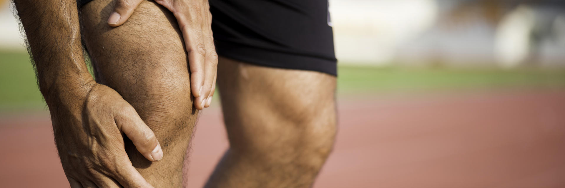 A sportsman with knee pain touching the painful knee area.
