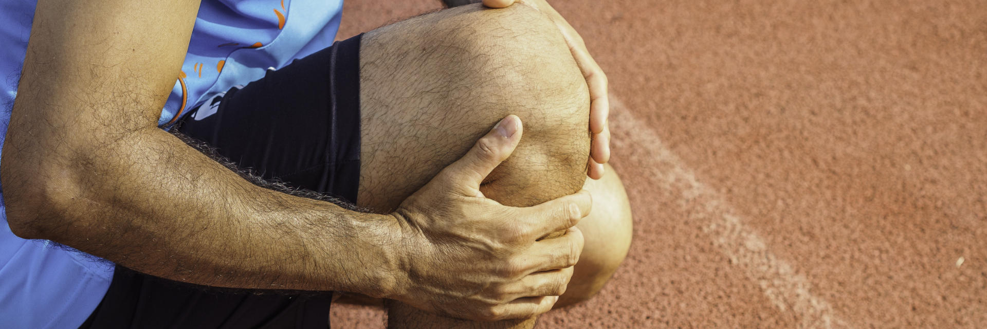 An athlete with knee pain touching the painful knee area.