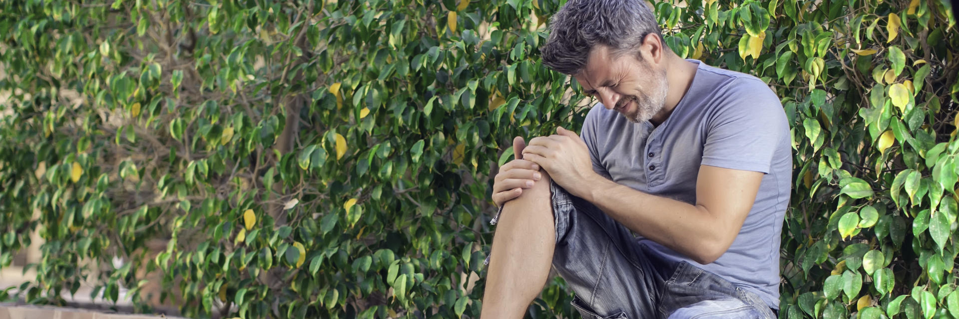 A man with severe knee pain touching the painful knee.