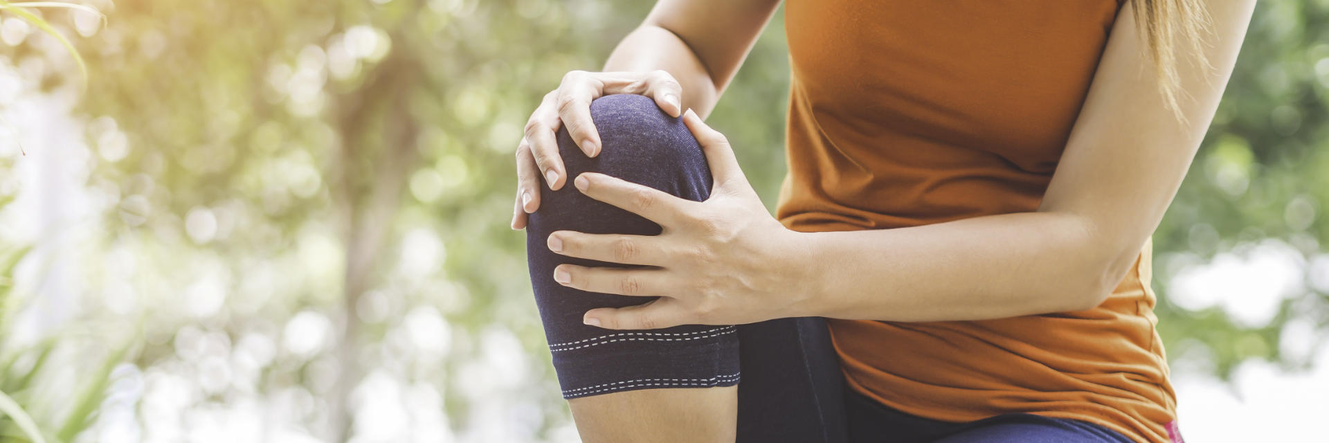 A woman with knee pain touching the painful knee.