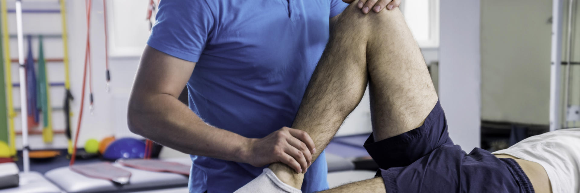 A physiotherapist examining patient's knee joint.