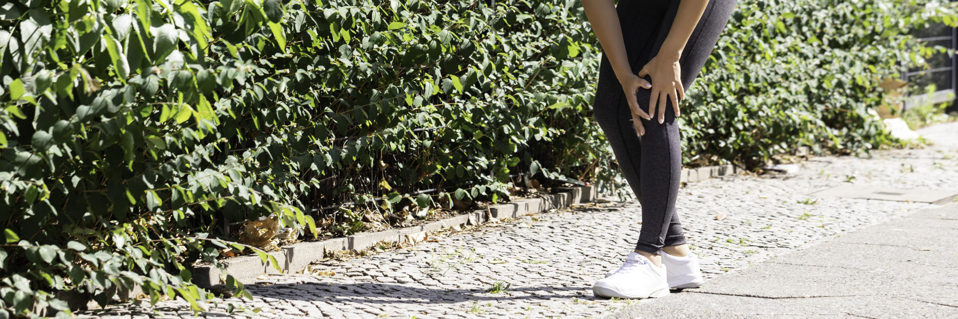A jogging woman with knee pain touching the painful knee.