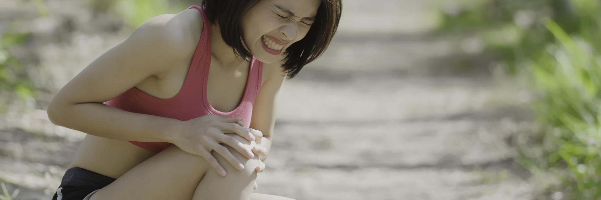 An injured sportswoman with severe knee pain touching the painful knee