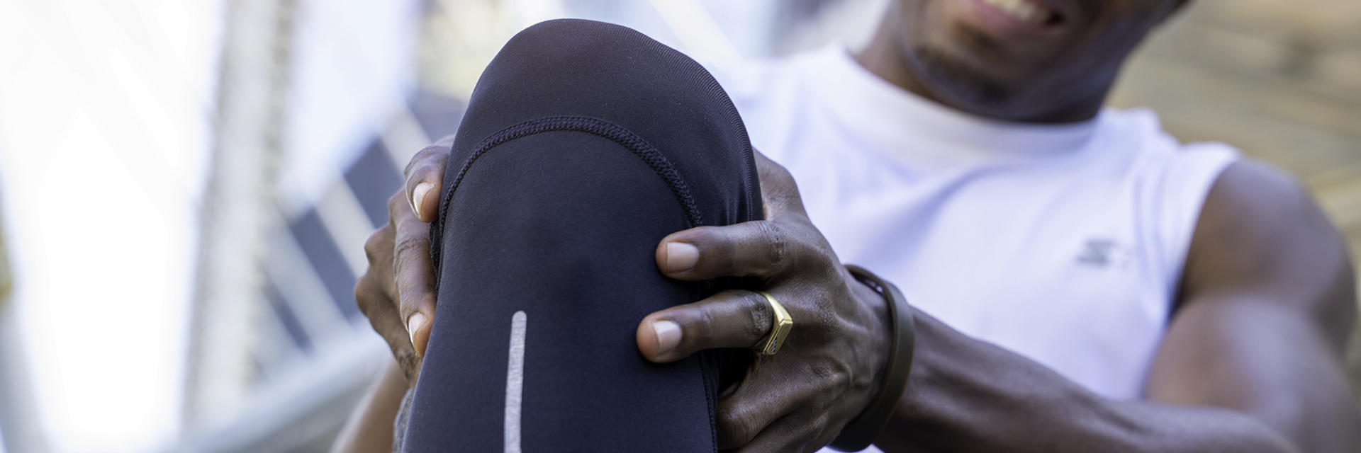 An Afro-American sportsman in pain touching the painful knee area.