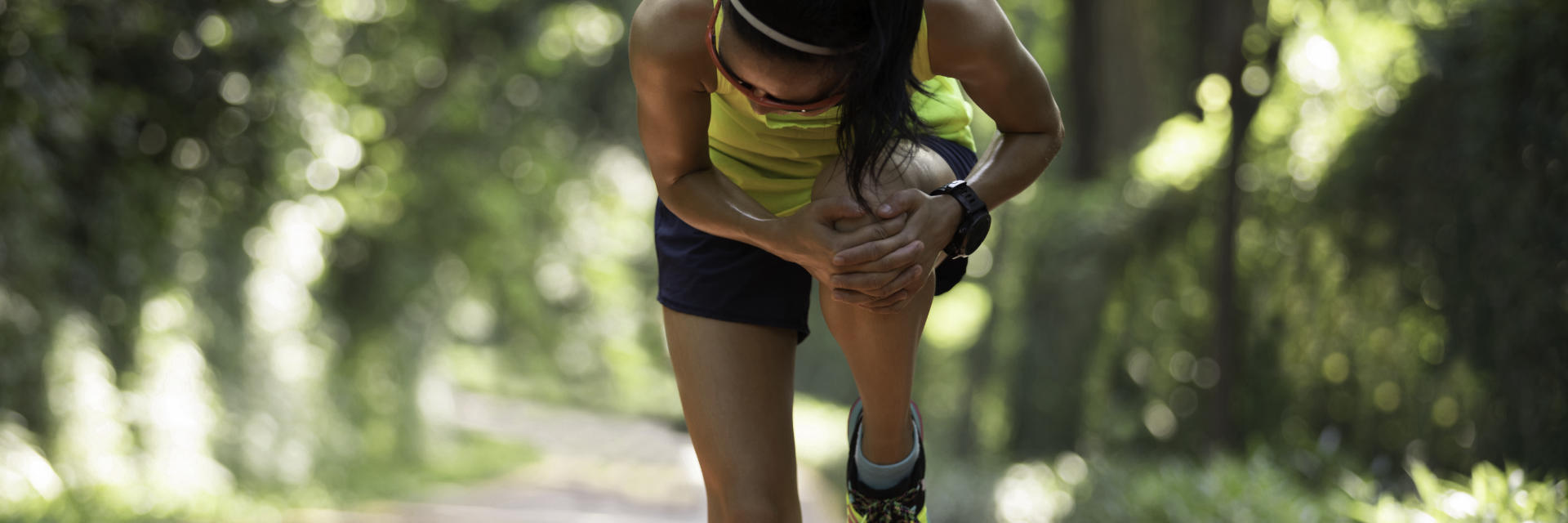 A runner stopped by unexpected knee pain gabbing her painful knee joint.