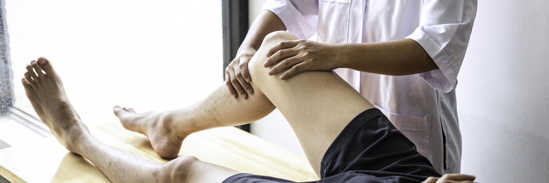 A physician examining patient's knee joint.