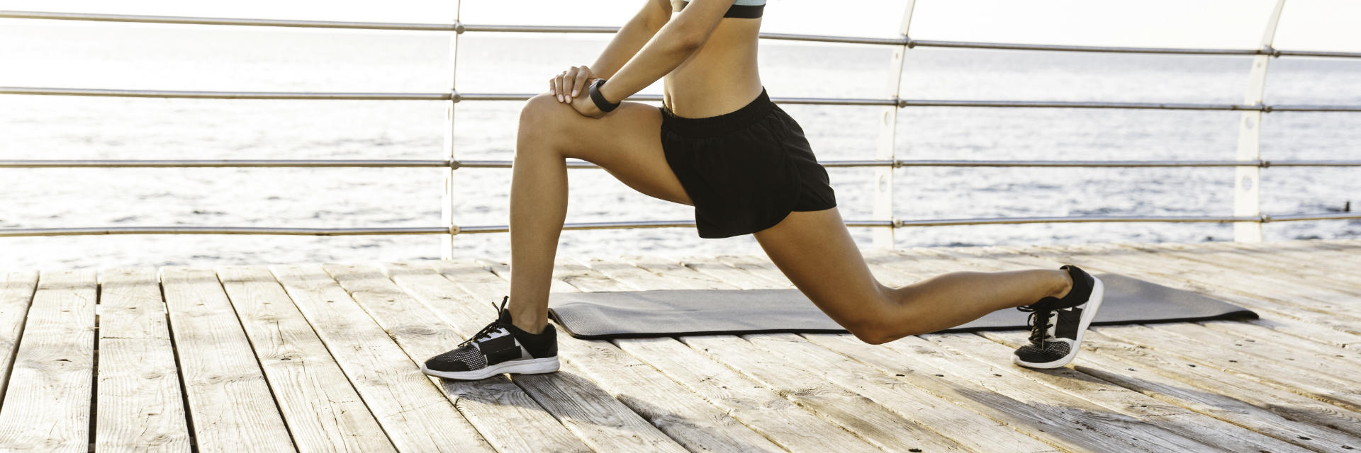 A fit sporty woman doing lunges on the pier.