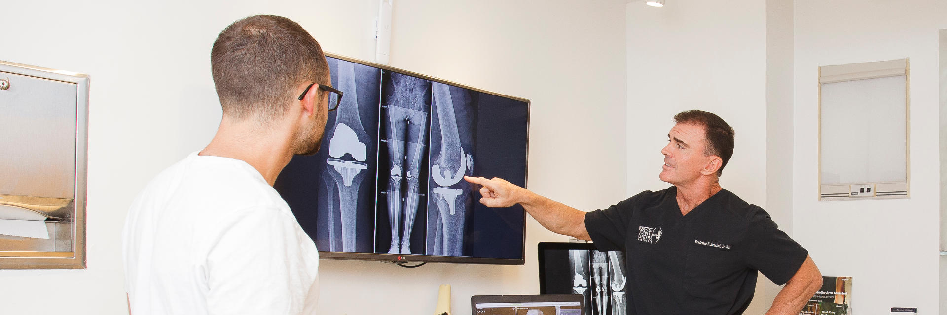 Dr. Buechel reviewing post-operative x-rays of his knee replacement patient.
