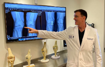 Dr. Buechel presenting pre and post-operative x-rays of his knee replacement patient.